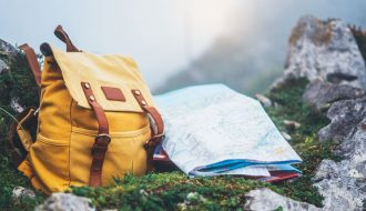 Photo d'un sac à dos et un carte de voyage avec vue sur la montagne