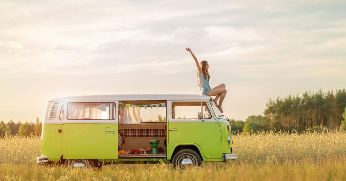 Une voyageuse sur son van dans un champ